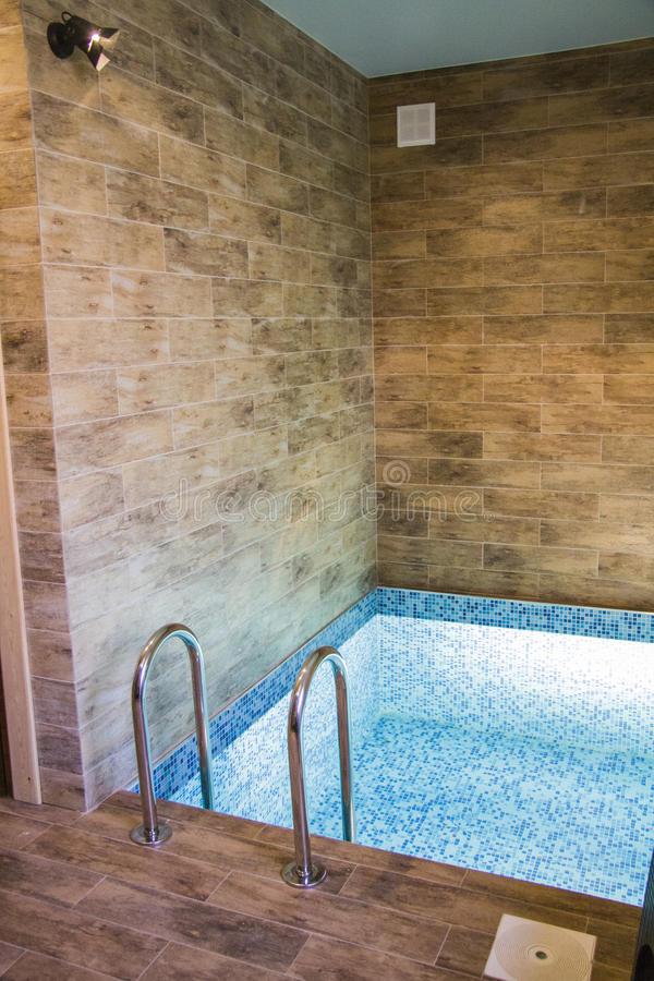 Мини-вариант бетонной чаши простой квадратной формы, построенной внутри помещения (сауна) и отделанной мозаикой