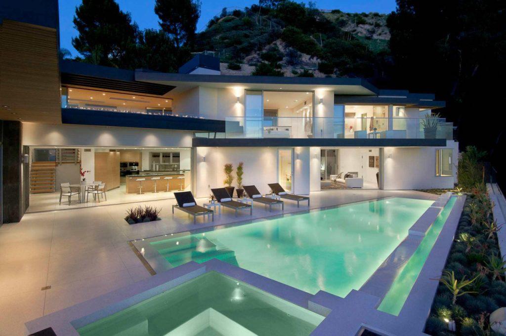 Бассейновая чаша с подсветкой на террасе украшает, как экстерьер дома, так и весь двор