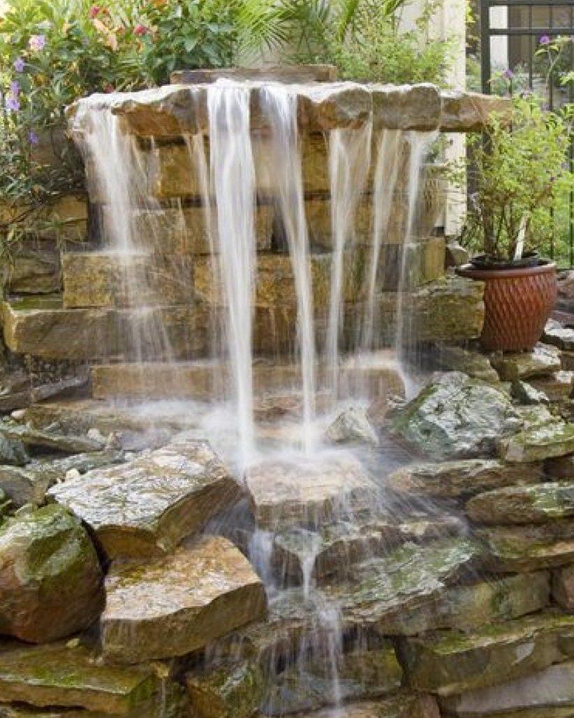Рукотворный водопад из природного камня прекрасно смотрится в саду