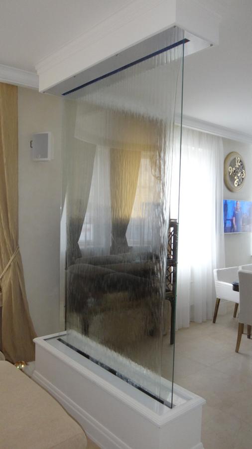 Безрамная водяная завеса на прозрачном стекле, заключенная в основу с пластиковой облицовкой выглядит элегантно и эффективно делит помещение на зоны