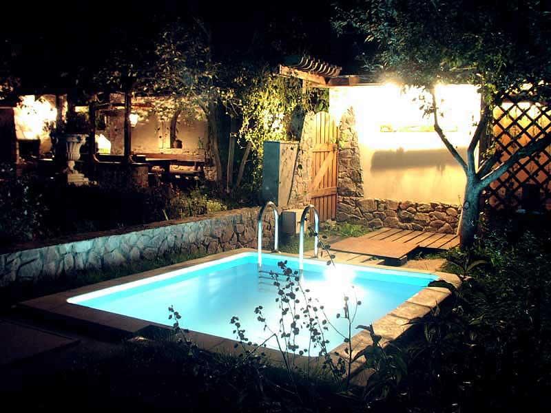 Система освещения бассейновой чаши привносит особый колорит в ландшафт обычного двора